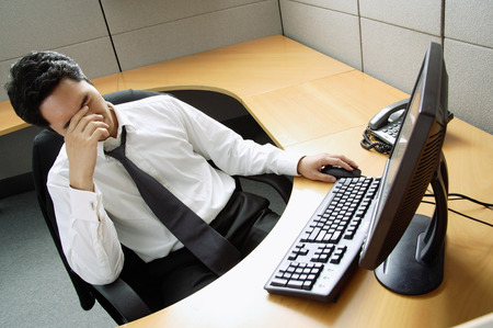 covering face: Businessman sitting at desk, hand covering face