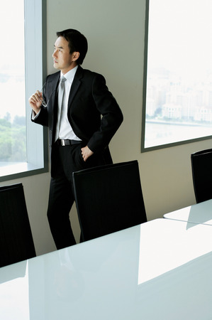 think through: Businessman standing next to window in conference room