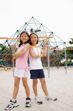 Girls at playground, standing back to back, smiling at camera Imagens