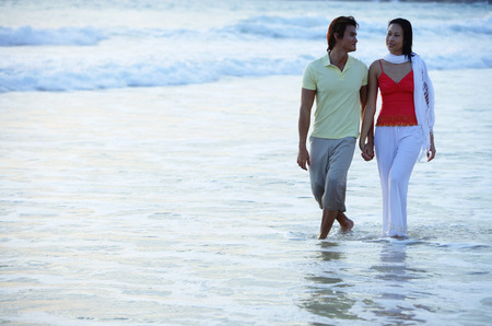 ankle deep in water: Couple walking on beach, ankle deep in water, holding hands
