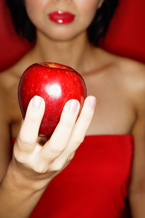 red tube: Woman in red tube tope holding red apple