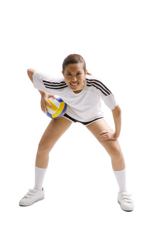 Young woman bending and holding volleyball