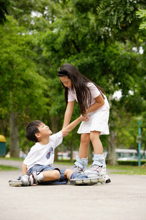 Children rollerblading, boy on the ground, girl pulling him up Stock Photo