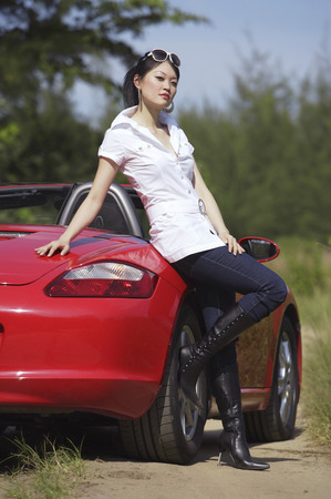 transportation: Woman leaning on red sports car LANG_EVOIMAGES