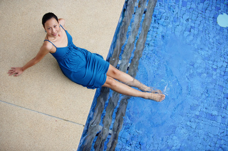 ankle deep in water: Young woman sitting by swimming pool, feet in water, smiling at camera