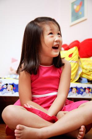 crosslegged: Young girl sitting cross-legged, looking away, smiling LANG_EVOIMAGES