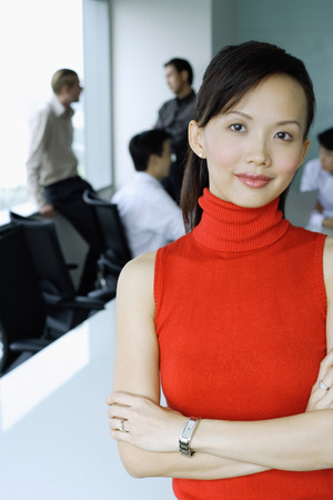 Female executive, looking at camera, people in the background