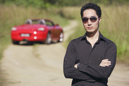 Man wearing sunglasses, arms crossed, facing camera, red sports car in the background