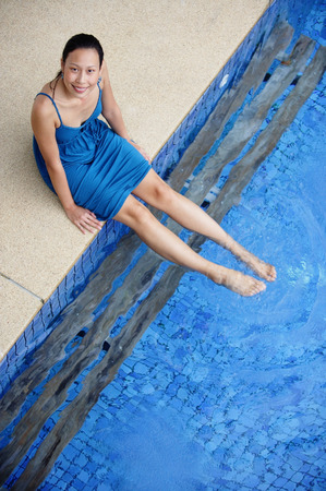 ankle deep in water: Young woman sitting by swimming pool, dipping feet in water, looking at camera LANG_EVOIMAGES