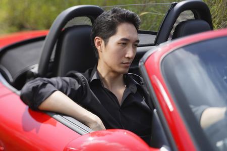 transportation: Man driving red convertible car LANG_EVOIMAGES