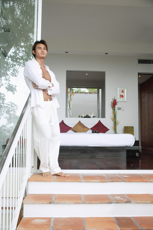 fully unbuttoned: Man standing on steps outside bedroom, arms crossed LANG_EVOIMAGES