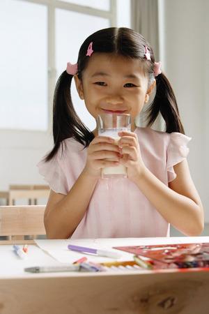 Girl holding glass of milk