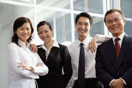 together with long tie: Business people standing side by side, smiling at camera LANG_EVOIMAGES