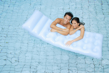 Couple in swimming pool leaning on pool raft