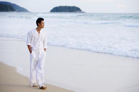 Man walking on beach, hands in pocket