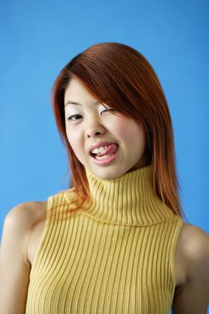 タートルネックを着ている女性、ウインクと舌を突き出して