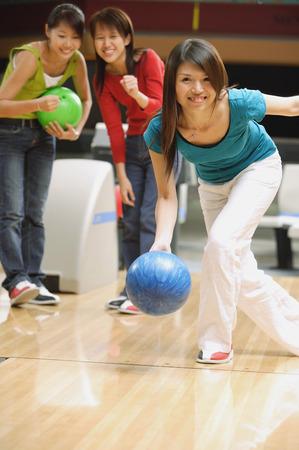 Vrouw bowling, vrienden achter haar, kijken