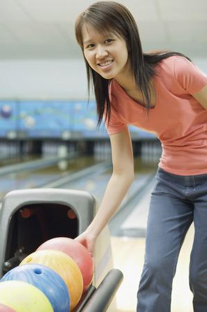 Woman at bowling alley selecting bowling ball, smiling at camera
