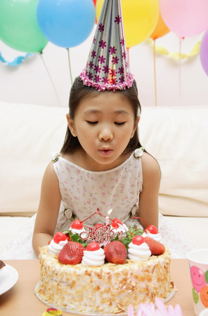 Girl blowing out candle on a cake LANG_EVOIMAGES