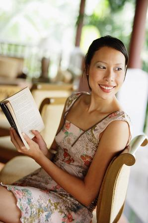 over the shoulder: Woman sitting, holding a book, looking over shoulder LANG_EVOIMAGES