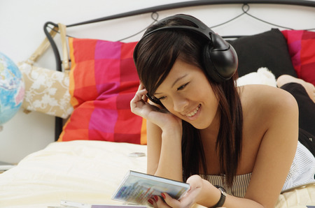 Girl lying on bed, holding CD case, listening to headphones