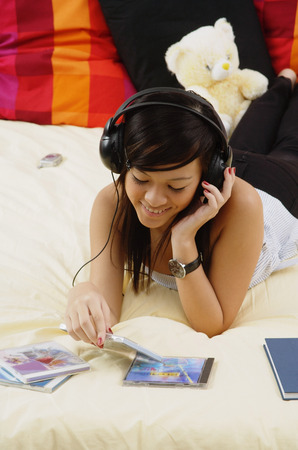Girl lying on bed, listening to headphones