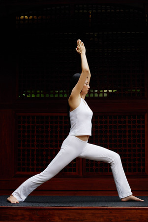 Woman stretching with both arms raised together above head, doing yoga pose, side shot