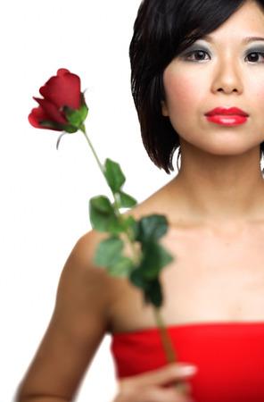 Woman holding single stalk of rose