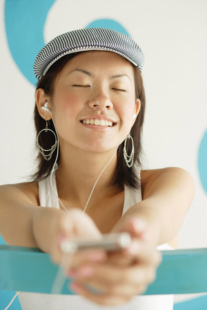 Young woman wearing beret, listening to MP3 player, eyes closed