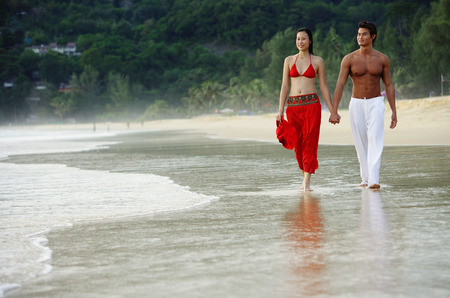 ankle deep in water: Couple walking side by side along beach, holding hands