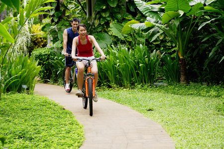 Couple cycling leisurely through a park