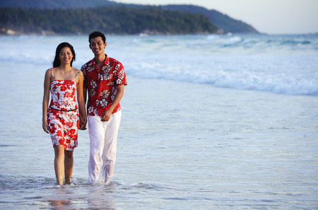 ankle deep in water: Couple walking on beach, ankle deep in water, holding hands, smiling at camera