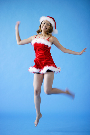 Woman in Santa hat and red dress, jumping