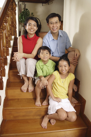 Family sitting on stairs, smiling at camera, portrait