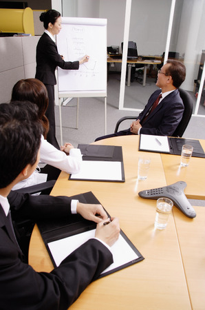 together with long tie: Business people in meeting, woman writing on flipchart