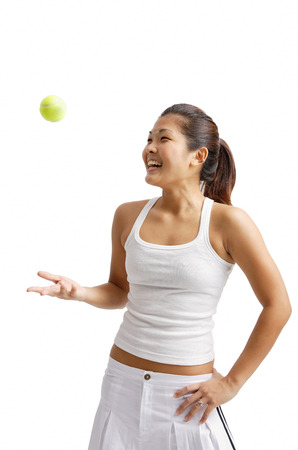 tossing: Young woman tossing tennis ball, hand on hip