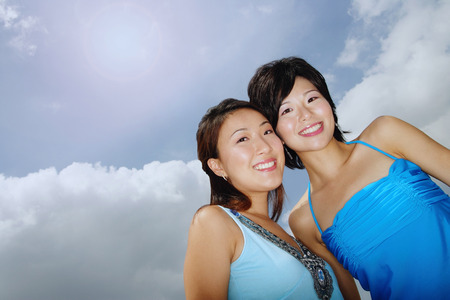 Two women standing cheek to cheek, smiling at camera, low angle view
