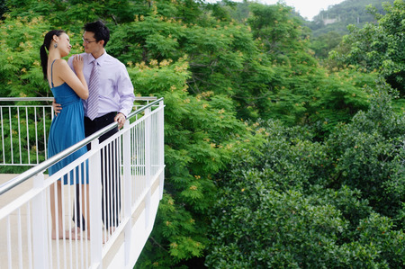 balcony: Couple standing on balcony, embracing LANG_EVOIMAGES