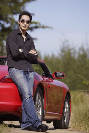 transportation: Man wearing sunglasses, arms crossed, leaning on red sports car