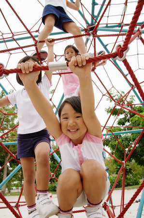 Four girls at playground, climbing on jungle gym Stock Photo