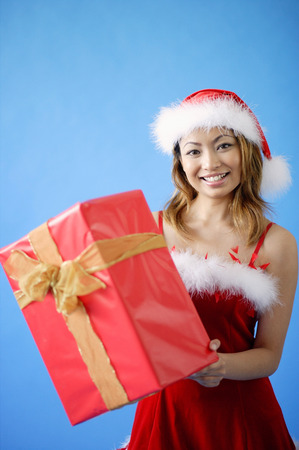 Woman in Santa hat, holding gift box