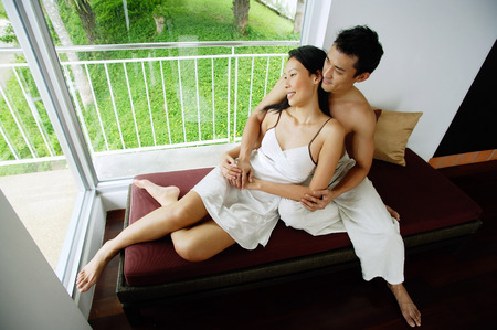 Couple sitting on daybed next to window, embracing