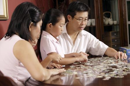 コーヒー テーブルの上のジグソー パズルを固定 4 人家族