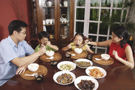 Family of four having dinner at home