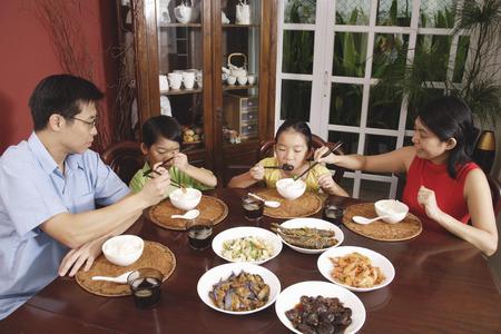 Familia de cuatro que tienen la cena en casa