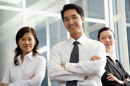 together with long tie: Executives standing with arms crossed, smiling at camera