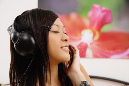 Girl listening to headphones, eyes closed, side view Imagens