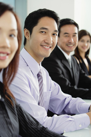 together with long tie: Business people sitting in a row, smiling at camera