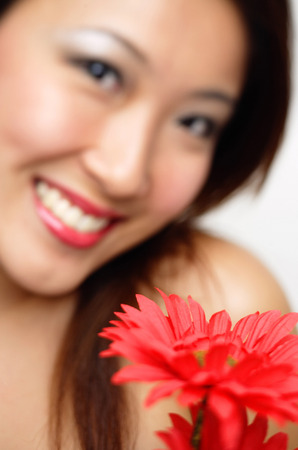 focus in foreground: Woman with flower, smiling, focus on the foreground