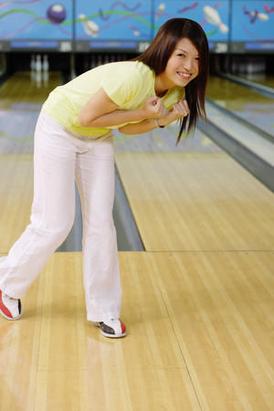 bending: Woman at bowling alley, bending over smiling